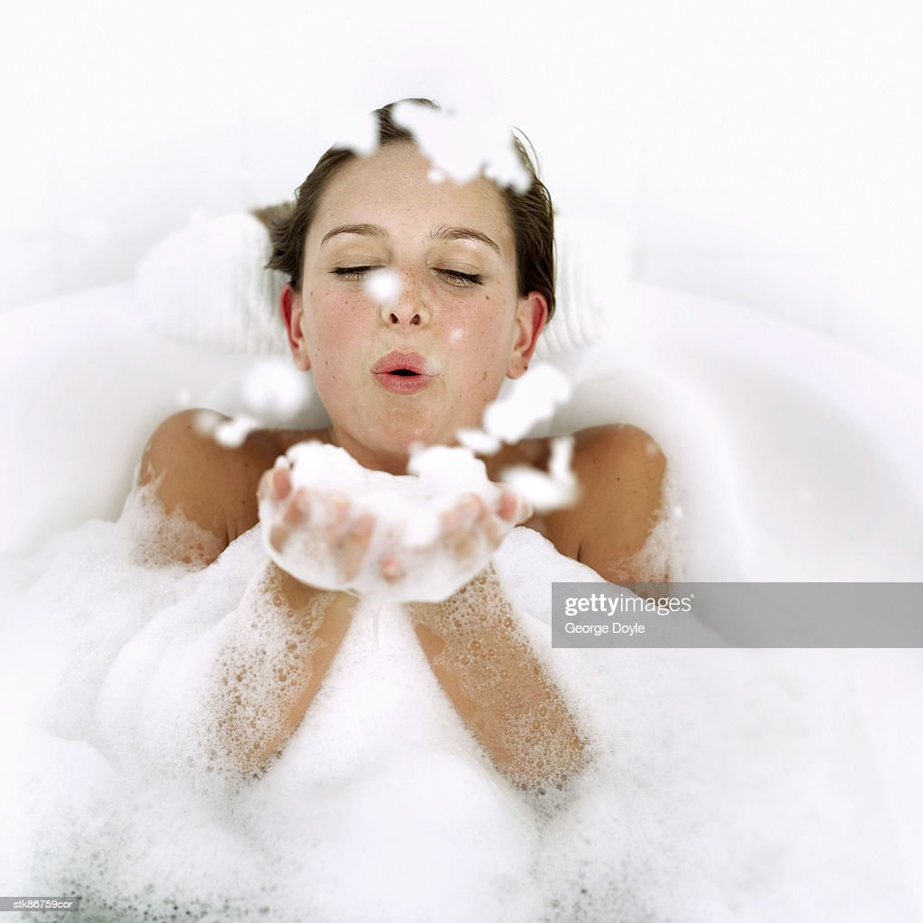 portrait of a young woman in a bathtub blowing foam from her hands : Stock Photo