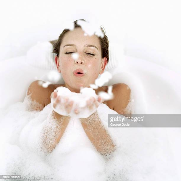 portrait of a young woman in a bathtub blowing foam from her hands