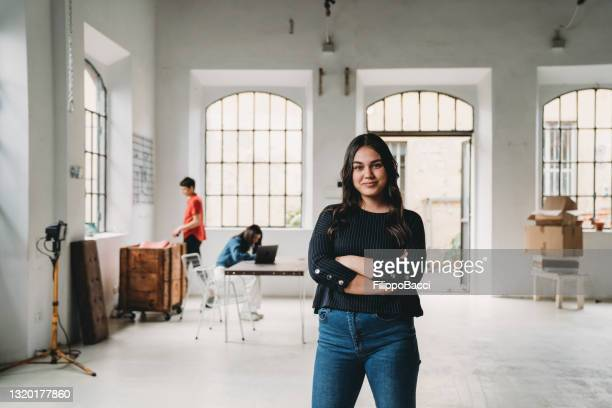 portrait of a young woman in a modern loft - founder stock pictures, royalty-free photos & images
