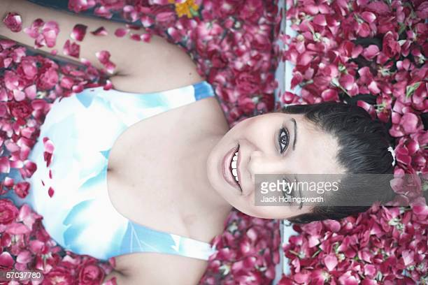 portrait of a young woman in a swimming pool filled with rose petals - indian cleavage stock pictures, royalty-free photos & images
