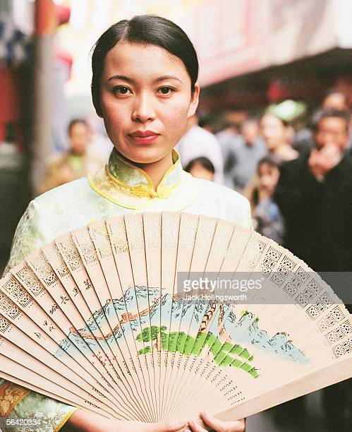 Portrait of a young woman in a traditional dress and holding a fan