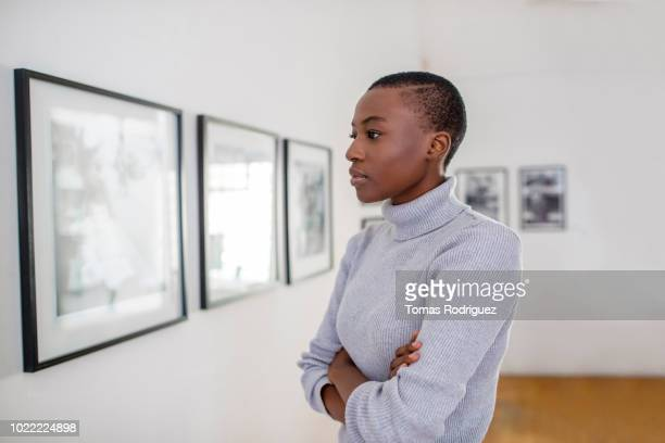 portrait of a young woman in an art gallery looking at pictures - museum curator stock pictures, royalty-free photos & images