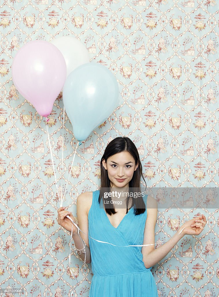 Portrait of a Young Woman in an Evening Gown Holding Balloons : Stock Photo