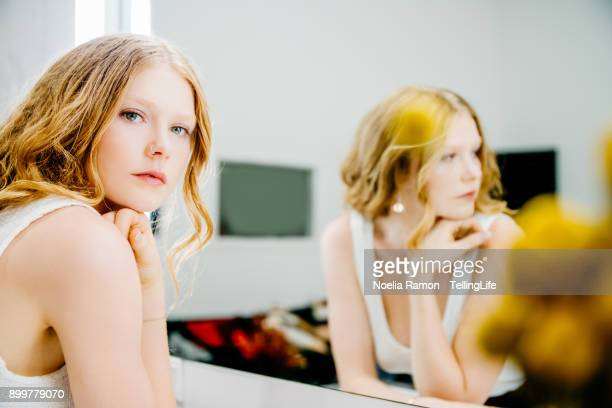 portrait of a young woman in front of a mirror - woman in mirror stock photos and pictures