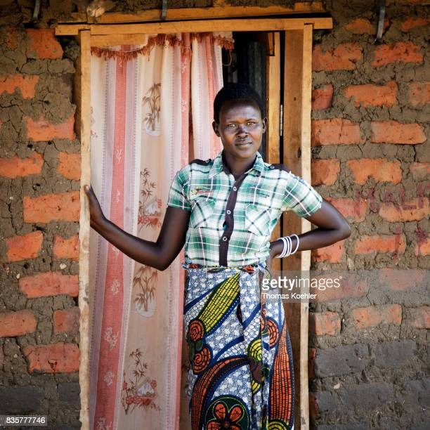 Portrait of a young woman in front of the entrance of her hut at the Rhino Refugee Camp Settlement in northern Uganda The area is home to about 90000...