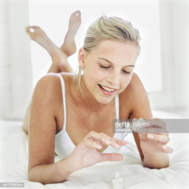 portrait of a young woman in her underwear painting her nails