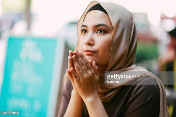 portrait of a young woman in malaysia - muslim praying stock pictures, royalty-free photos & images