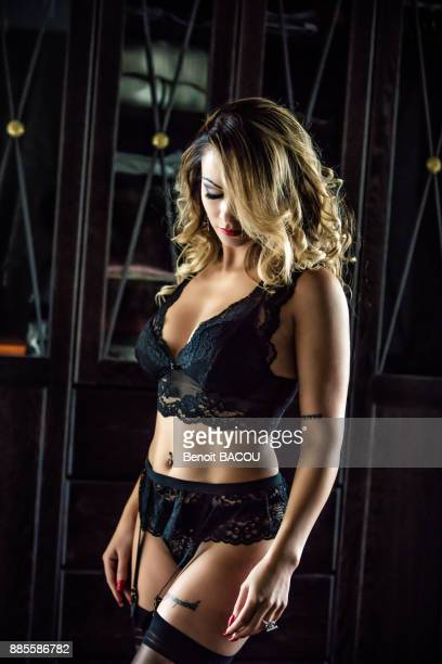 portrait of a young woman in profile in black lingerie, head down, eyes closed - stockings and suspenders - fotografias e filmes do acervo