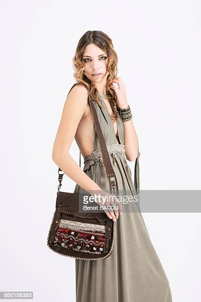 portrait of a young woman in profile, wearing a handbag and a beige dress sanhadja - beige purse stock pictures, royalty-free photos & images