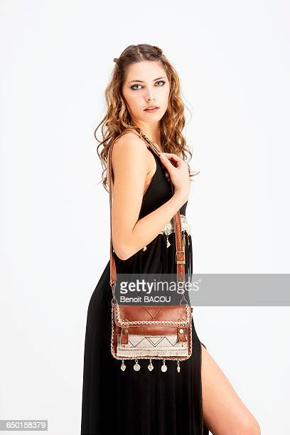 portrait of a young woman in profile, wearing a handbag and a black dress sanhadja - black purse stock photos and pictures