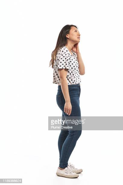 portrait of a young woman in studio - standing stock-fotos und bilder