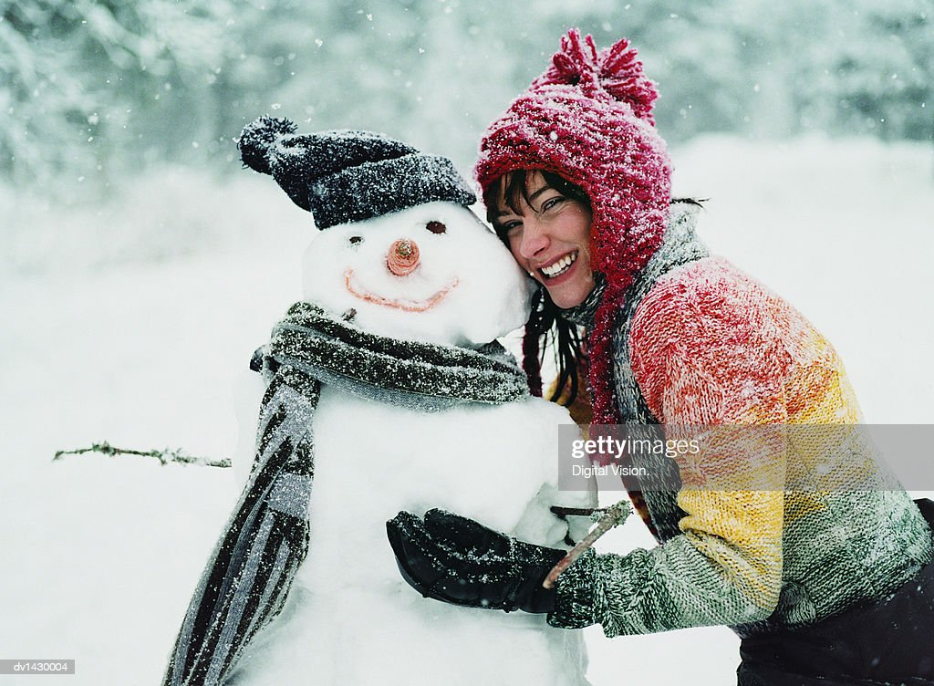Portrait of a Young Woman in the Snow Next to a Snowman : Stock Photo