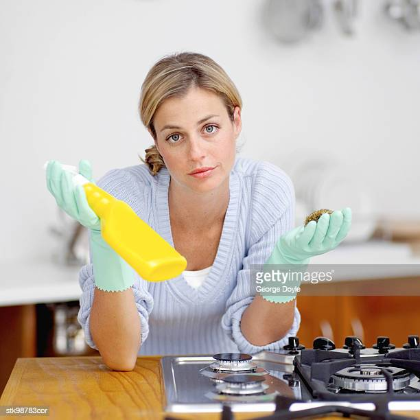 portrait of a young woman in wash gloves holding a bottle of liquid detergent