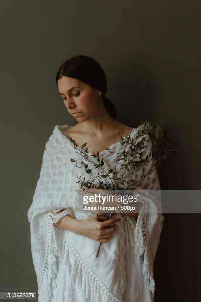 portrait of a young woman in white shawl holding branches and leaves - shawl stock pictures, royalty-free photos & images
