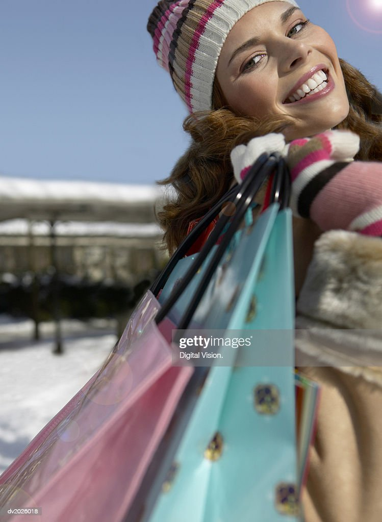 Portrait of a Young Woman in Winter Clothing Carrying Shopping Bags : Stock Photo
