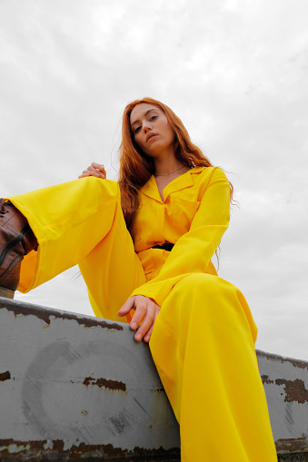Portrait of a young woman in yellow clothes against the sky - gettyimageskorea