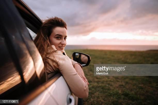 retrato de una joven dentro de un coche al atardecer - cielo melancólico fotografías e imágenes de stock