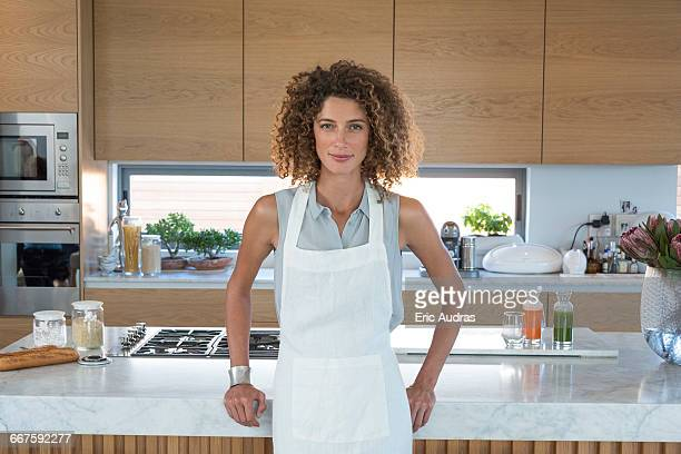 portrait of a young woman leaning against kitchen counter - waist up stock pictures, royalty-free photos & images