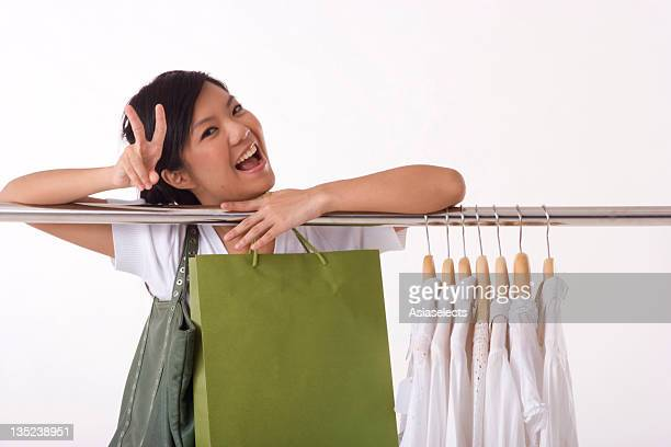 Portrait of a young woman leaning on a clothes rack