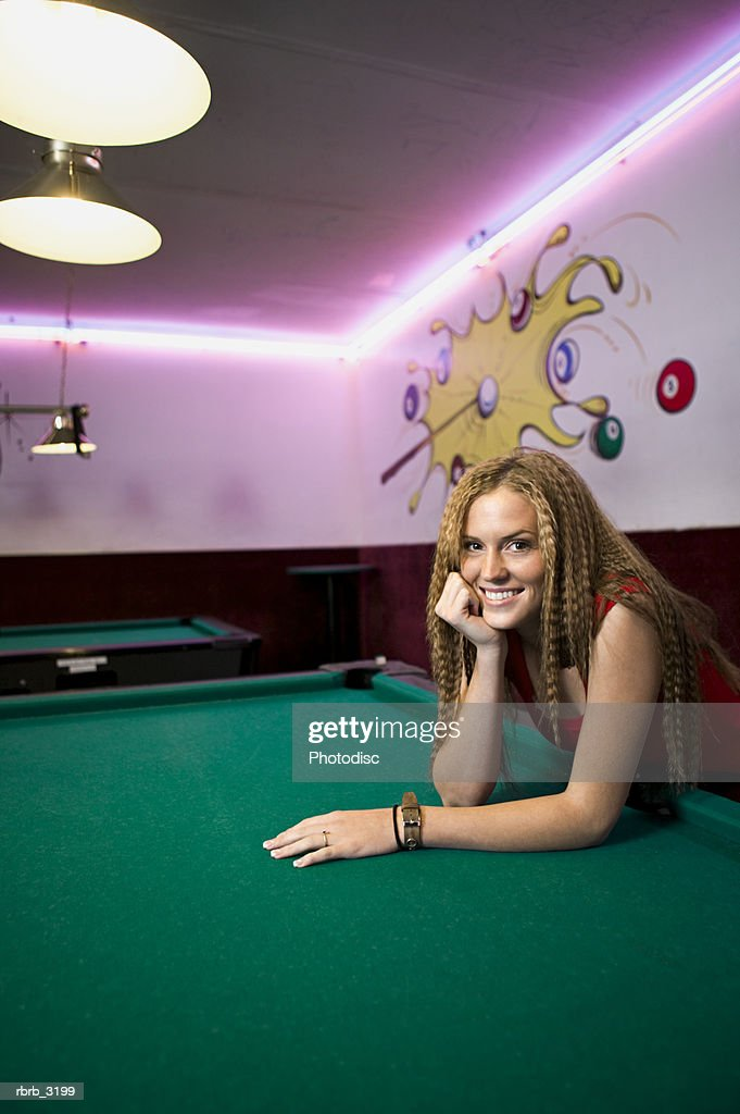 Portrait of a young woman leaning on a pool table : Foto de stock