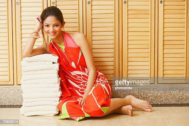 Portrait of a young woman leaning over a stack of towels and smiling