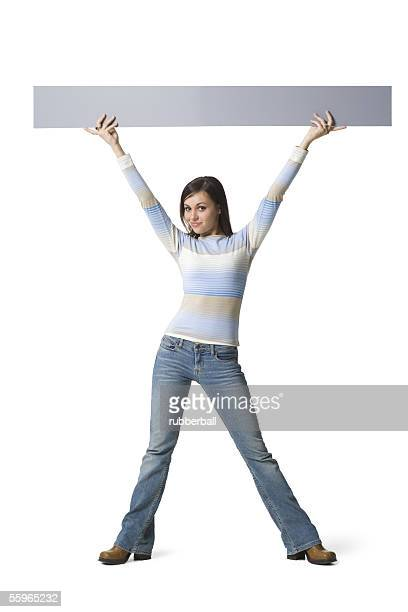 portrait of a young woman lifting up a placard - 足を開く ストックフォトと画像