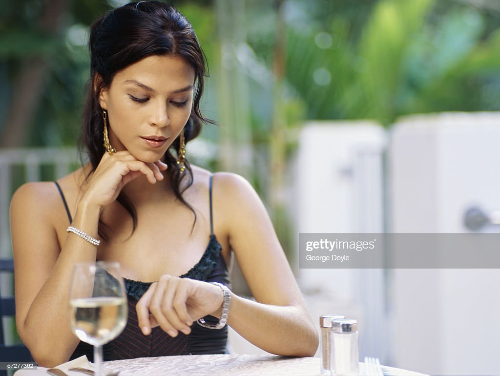 Portrait of a young woman looking at her watch : Stock Photo