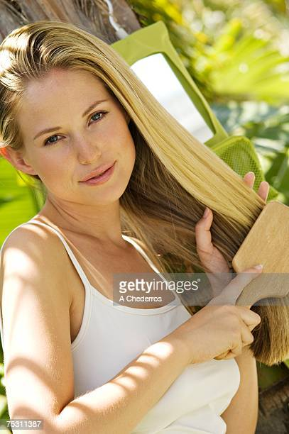 Portrait of a young woman looking at the camera, brushing her hair outdoors