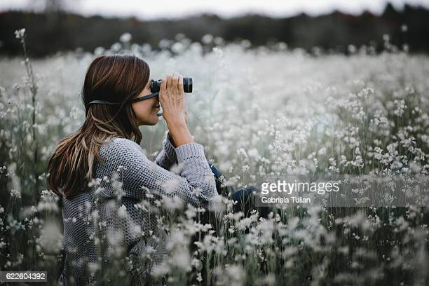 Portrait of a young woman looking through the binoculars