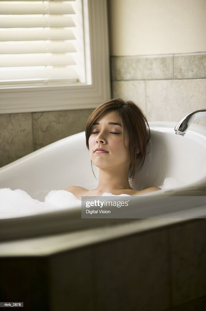 Portrait of a young woman lying in a bathtub with her eyes closed : Foto de stock