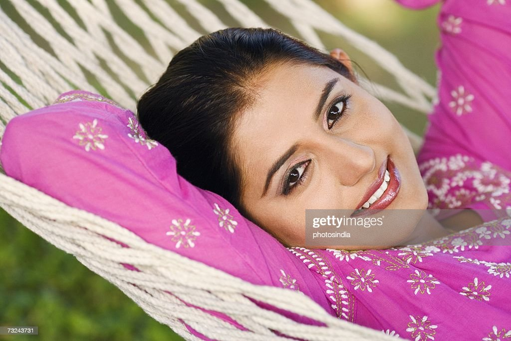 Portrait of a young woman lying in a hammock and smiling : Stock Photo