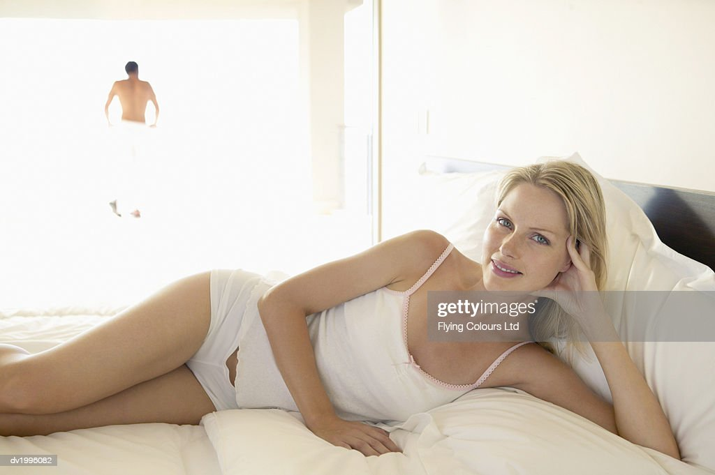 Portrait of a Young Woman Lying on a Bed in Her Underwear : Stock Photo