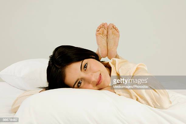 portrait of a young woman lying on a bed - soles pose stock pictures, royalty-free photos & images