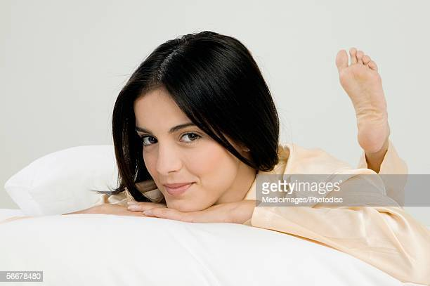 portrait of a young woman lying on a bed - soles pose stock photos and pictures