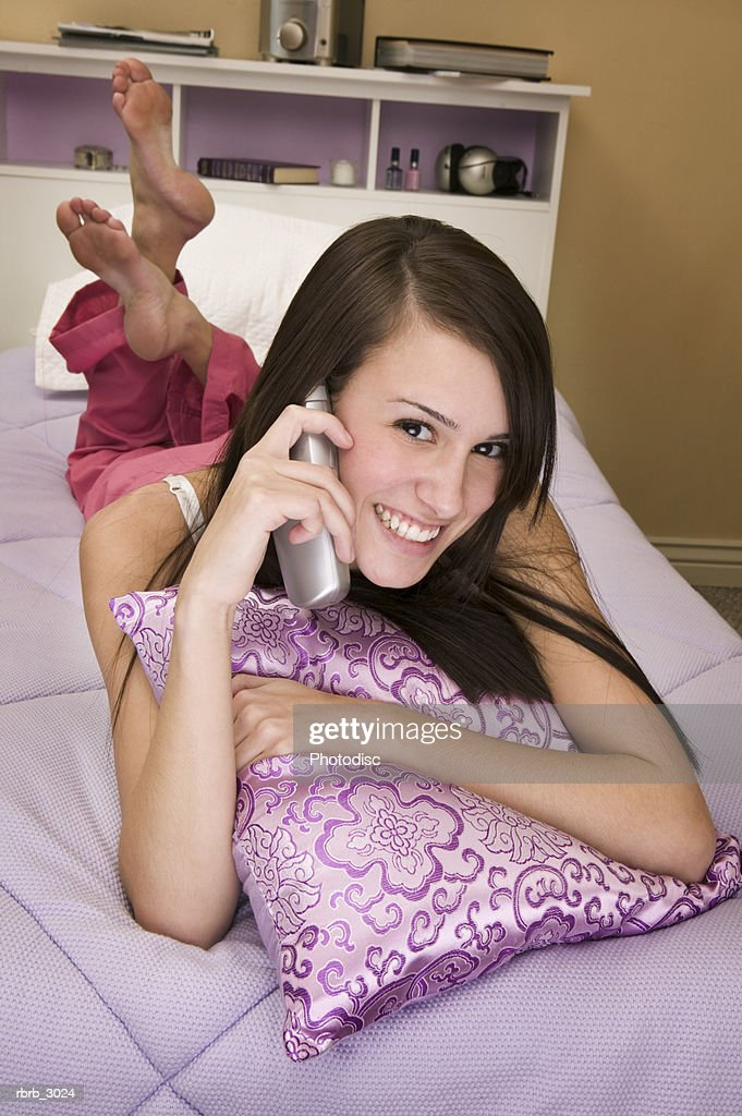 Portrait of a young woman lying on a bed talking on a mobile phone : Foto de stock