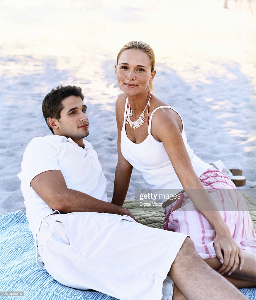 Portrait of a Young Woman Lying on a Blanket on a Beach With a Man : Stock Photo