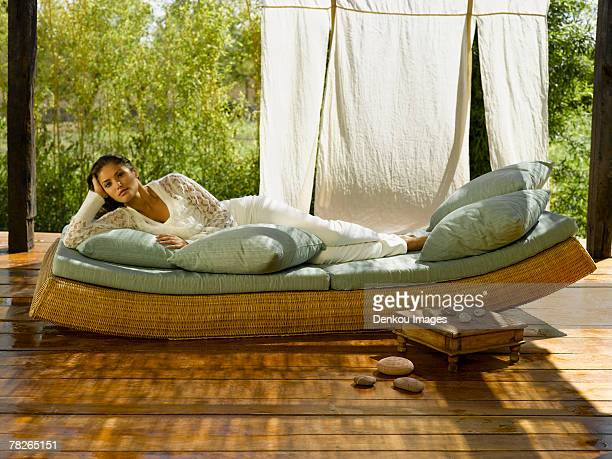 Portrait of a young woman lying on a chaise lounge