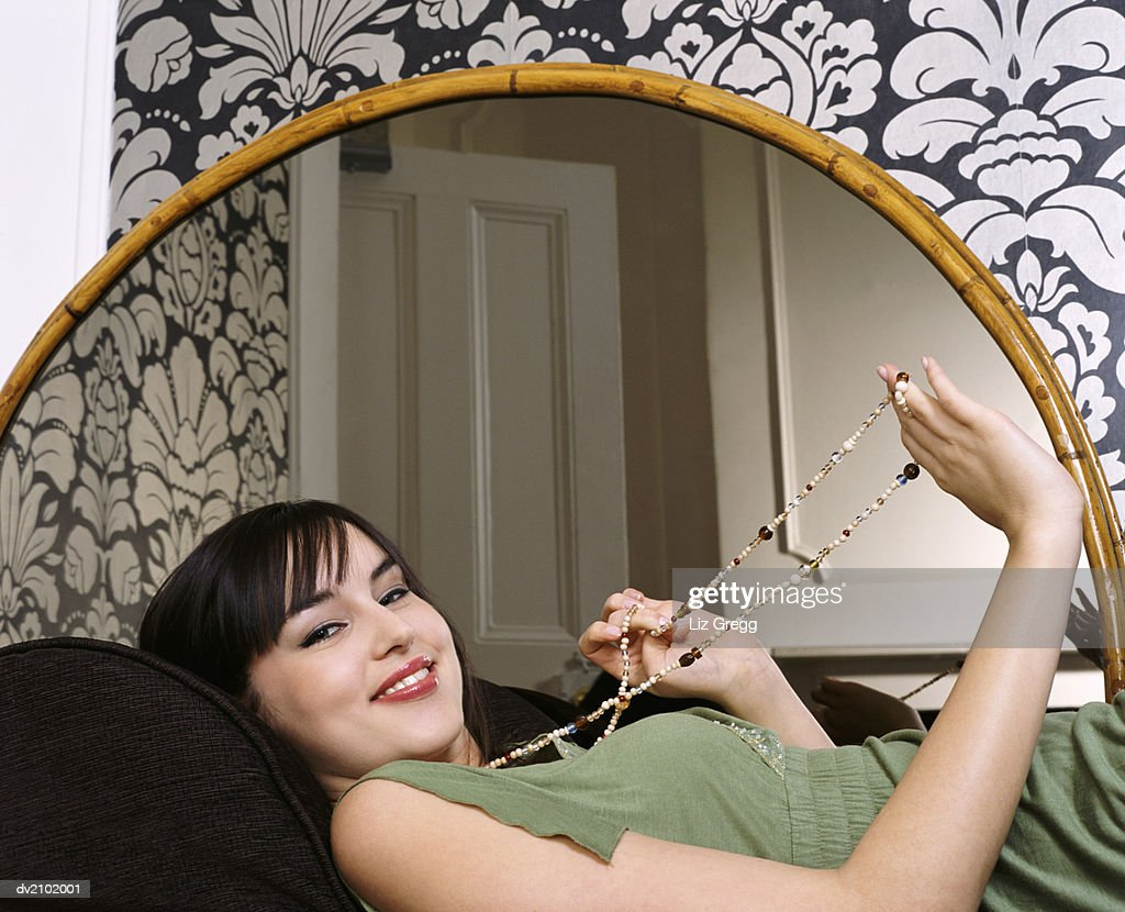 Portrait of a Young Woman Lying on a Couch by a Mirror, Wearing a Bead Necklace : Stock Photo