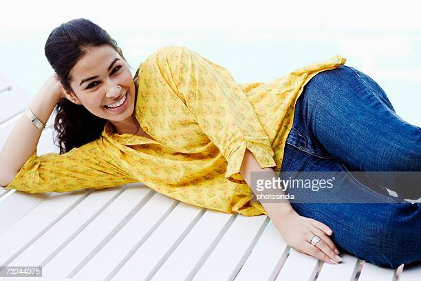Portrait of a young woman lying on a lounge chair and smiling