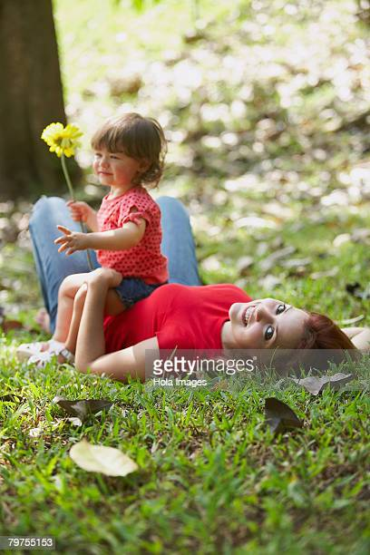 Portrait of a young woman lying on grass with her daughter sitting on her stomach