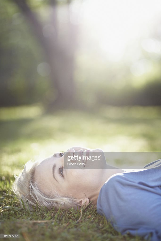 portrait of a young woman lying on the lawn : Stock Photo