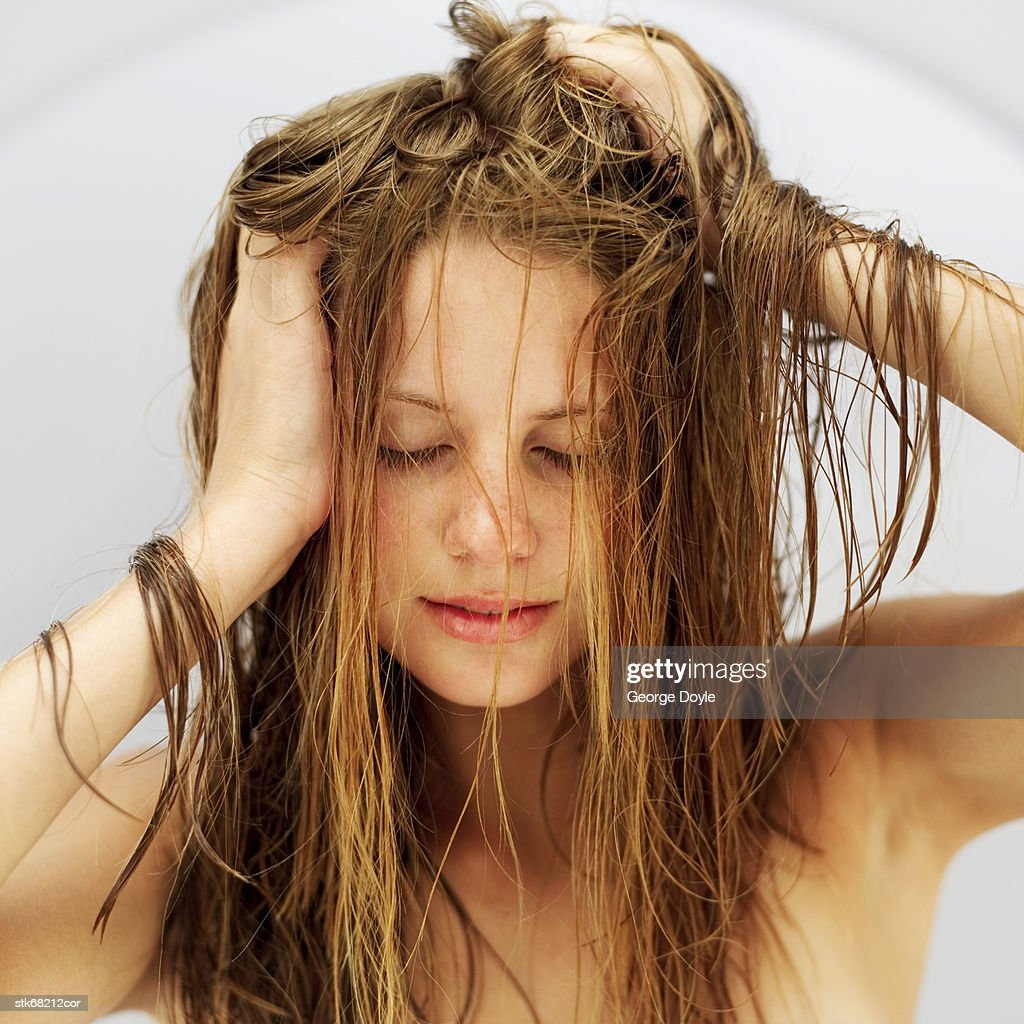 portrait of a young woman massaging her head with her eyes closed : Stock Photo