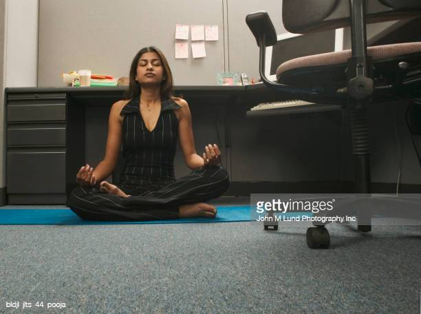Portrait of a young woman meditating on the floor of an office