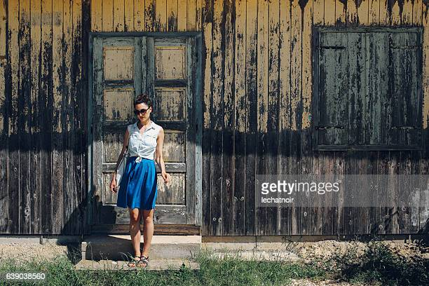 Portrait of a young woman next to old wooden house