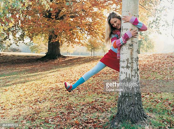 Portrait of a Young Woman on one Leg Laughing With Her Arms Around a Tree