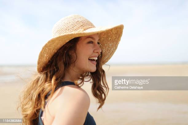 portrait of a young woman on the beach - hat stock pictures, royalty-free photos & images