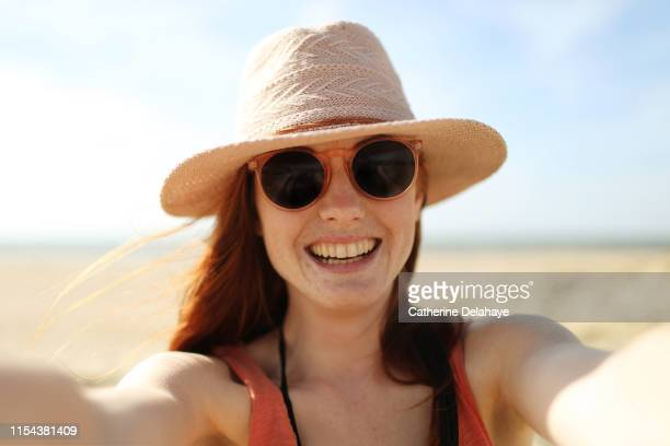 portrait of a young woman on the beach - sunglasses stock pictures, royalty-free photos & images