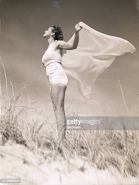 Portrait of a young woman on the beach She is shown fulllength in profile holding a scarf behind her in the wind Undated photograph circa 1950's