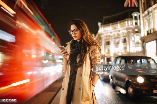 portrait of a young woman on the busy streets of london downtown in the evening, texting for a cab - long exposure stock pictures, royalty-free photos & images