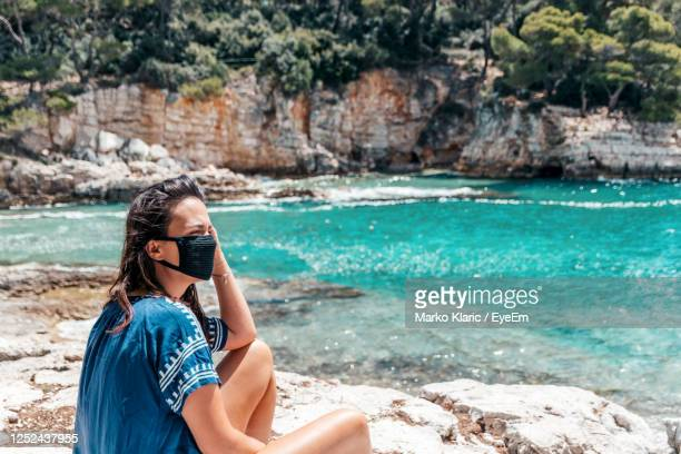 portrait of a young woman on vacation during corona virus crisis. protective mask, sea, beach. - croatia stock pictures, royalty-free photos & images